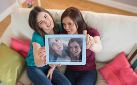 Two smiling friends on the couch taking a selfie with tablet pc at home in the living room photo