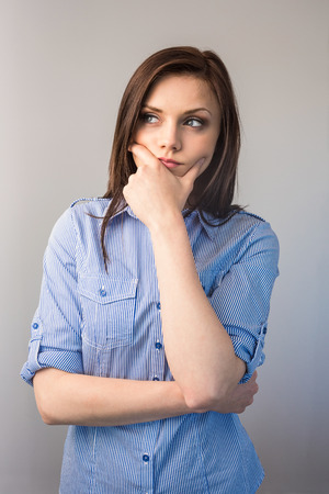 Pensive serious brunette posing on grey background photo