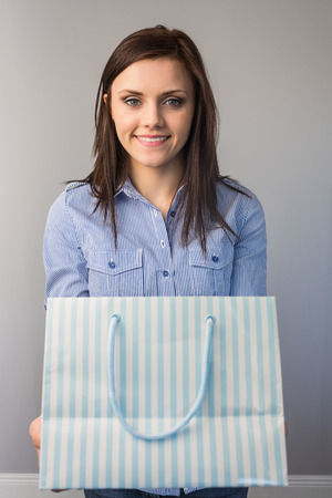 Cheerful pretty brunette on grey background offering a present photo