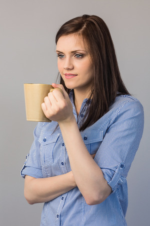 Pensive pretty brunette on grey background holding cup of coffee photo