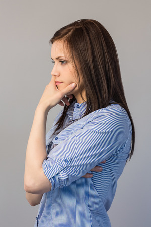Thoughtful pretty brunette posing on grey background photo