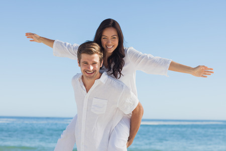 short wave: Woman sitting on mans back smiling at camera at beach on a sunny day Stock Photo