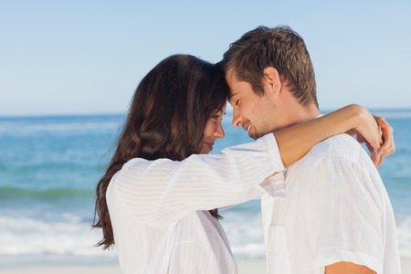 facing away: Couple embracing each other on the beach against ocean on sunny day Stock Photo
