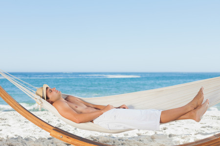 Handsome man relaxing in a hammock on the beach behind on holidays photo