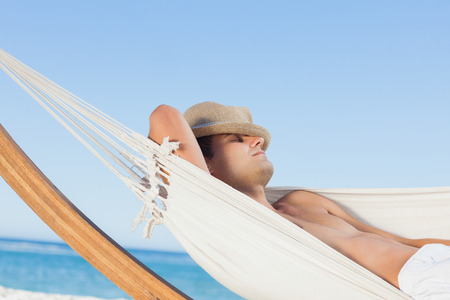 Man lying on hammock sleeping with straw hat on face on holidays photo