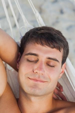 Peaceful man sleeping in hammock on holidays photo