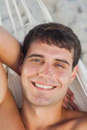 Attractive man lying in hammock looking at camera on holidays photo