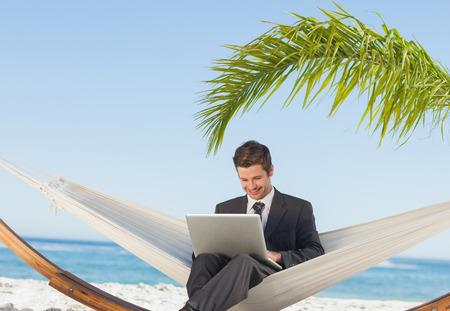 hammock: Sonriente hombre de negocios con ordenador port�til y sentado en la hamaca en la playa Foto de archivo