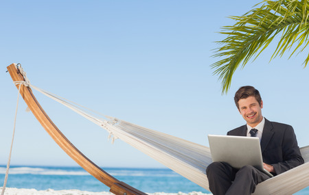 Businessman sitting in hammock using laptop looking at camera on beach photo