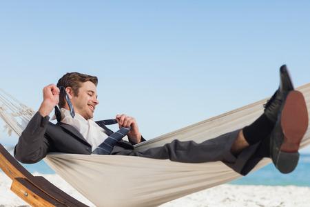 hamaca: Empresario sonriente acostado en la hamaca quitándose la corbata en la playa