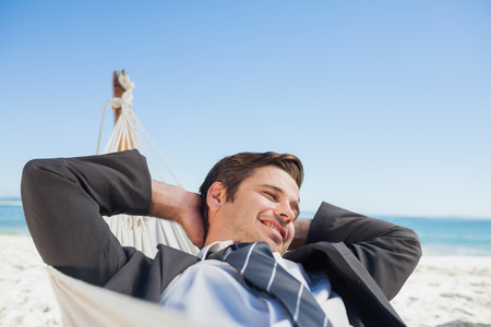Businessman relaxing in hammock at beach on sunny day photo