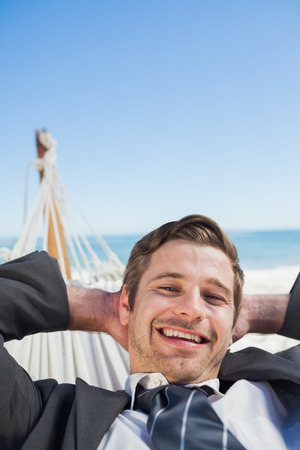 Smiling businessman relaxing in hammock looking at camera on sunny day photo