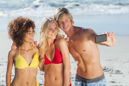 Man taking a photo with two friends on the beach on holidays photo