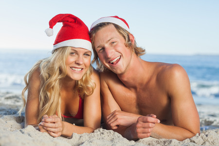 Couple lying on beach wearing christmas hats and looking at camera photo