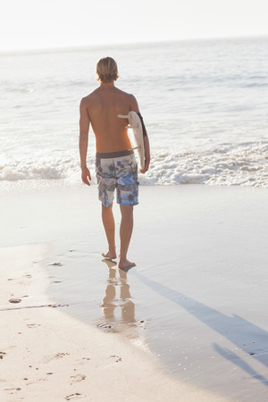 Rear view of man holding surfboard on beach walking out to sea photo