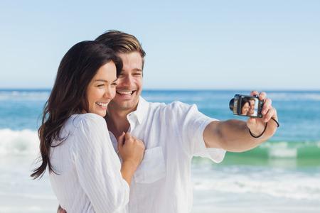 personas tomando agua: Pares felices que toman una foto en una playa en las vacaciones Foto de archivo