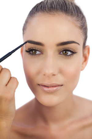 Smiling attractive woman applying make up on her eyebrows on white background photo