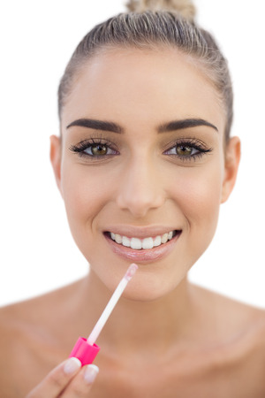 Delighted attractive woman applying gloss on her lips on white background photo