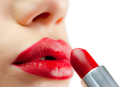 Extreme close up on red lips being made up on white background photo