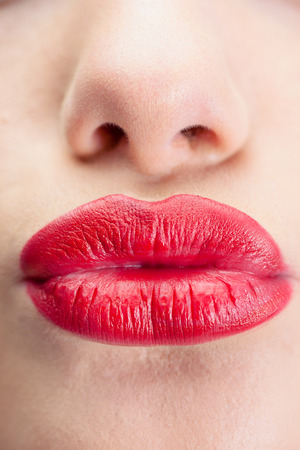 Extreme close up on gorgeous voluminous red lips kissing at camera photo