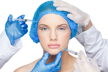 surgical cap: Surgeons making injection on pretty blonde wearing blue surgical cap on white background