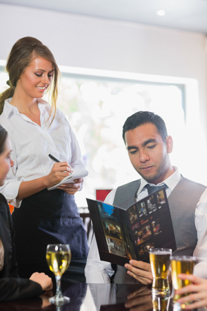 Businessman ordering a dinner from smiling waitress in a restaurant photo