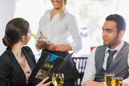 Businesswoman ordering dinner from smiling waitress in a restaurant photo