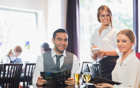 alcohol server: Business people and waitress smiling at camera in restaurant