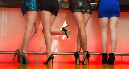 piernas sexys: Mujeres sexy piernas se colocan de nuevo a la cámara y posando en el bar en la discoteca Foto de archivo