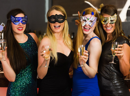 Laughing friends wearing masks holding champagne glasses looking at camera