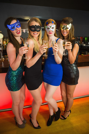 hedonism: Happy friend with masks on holding champagne smiling at camera Stock Photo