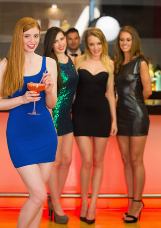 Beautiful woman standing in front of her friends holding cocktail and looking at camera photo