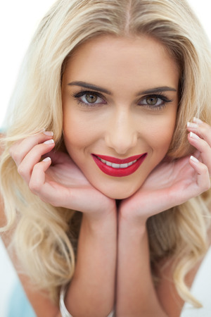 Close up of a smiling blonde model looking at camera on white background photo