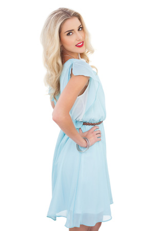 Pretty blonde model in blue dress posing hand on the hip on white background photo