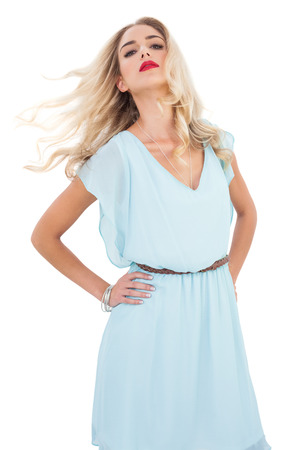 Attractive blonde model in blue dress posing shaking her hair on white background photo