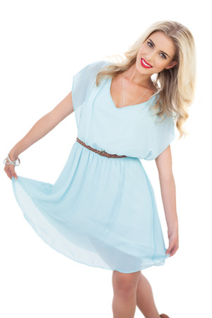 Delighted blonde model in blue dress posing holding her dress on white background photo