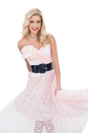 Pleased blonde model in pink dress posing shaking her dress on white background photo