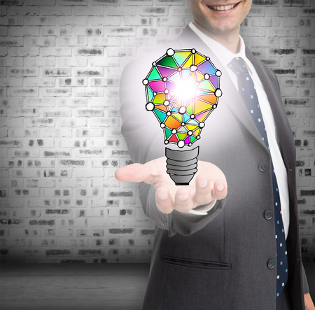 Close up of businessmans hand showing holographic light bulb in front of brick lined wall photo