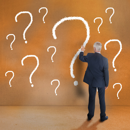Mature businessman touching question mark on beige wall photo