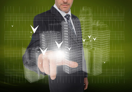 Businessman pointing at holographic faint city on green background
