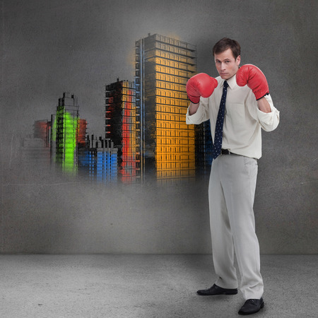 Businessman with boxing gloves standing in front of grey wall showing colorful city photo