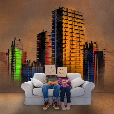 Couple sitting on couch in front of colored painted city in bronze light photo