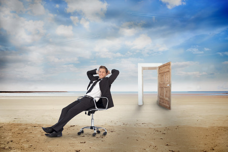 Businessman on swivel chair on the beach with wooden door photo