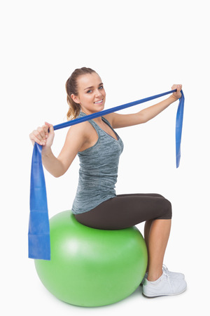 ball stretching: Attractive young woman sitting on therapy ball stretching her arms with a resistance band