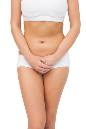body concern: Slim young woman wearing a sports bra posing on white background