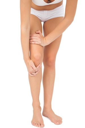 Young woman touching her injured knee on white background photo