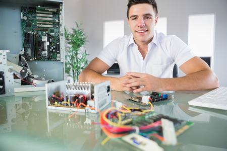 it technician: Attractive computer engineer sitting at desk smiling at camera in bright office Stock Photo