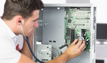 Handsome computer engineer examining hardware with stethoscope in bright office photo