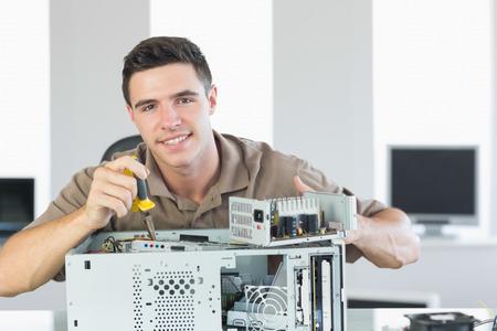 maintenance man: Handsome cheerful computer engineer repairing open computer in bright office