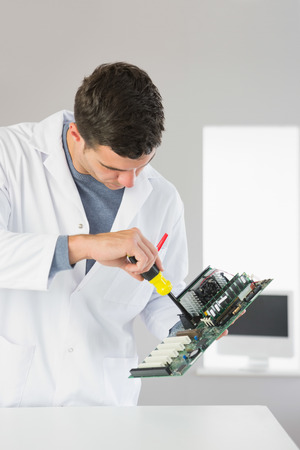 Attractive computer engineer repairing hardware with screw driver in bright office photo